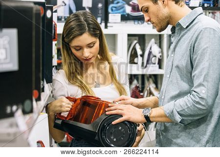 Cropped View Of A Side View Of A Young Man And A Woman Choosing A Vacuum Cleaner In A Home Appliance