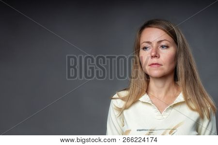 Woman Emotion. Woman In Serious Reflection With Her Eyes Down. Portrait Of Girl With Loose Blond Hai