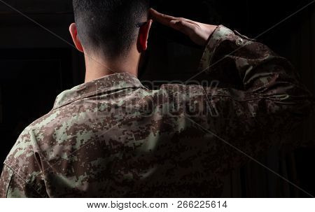 Young Soldier Saluting Standing On Black Background