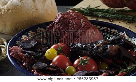 Meat cutting on plate with tomatoes. Scene. Close up of plate with exquisite cut ham and meat with tomatoes. Meat culinary dish on background of fresh herbs and bread. poster