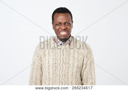 Displeased African Man Frowns Face With Displeasure, Has Irritated Expression And Clenches Teeth