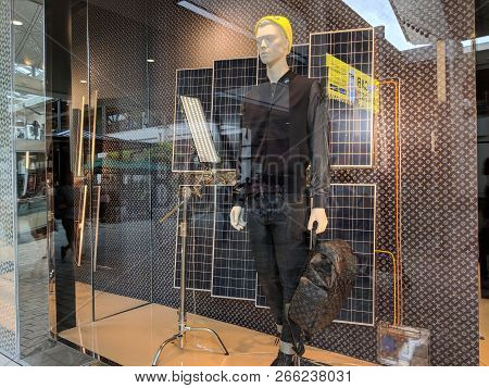 Honolulu - May 31, 2018:  Male Figure Holds Bag In Louis Vuitton Window Display With Solar Panels Po