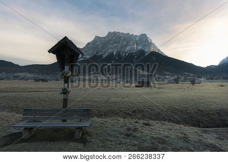 Vintage Wooden Bench And An Old Cross, On A Meadow With Frosty Grass, In The Alps Mountains, Near Eh