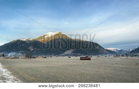The Austrian Alps Mountains, A Village, And Scattered Barns On A Meadow With Frozen Grass, Near Ehrw