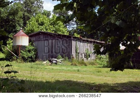 Old Run Down Barn And Metal Red Roofed Silo