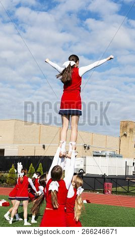 High School Cheerleaders Practice A Routine Beore Homecoming With Three Girls Balancing Their Teamma