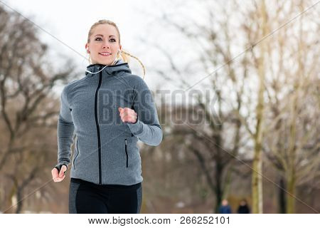 Woman running or jogging down a path on winter day in park