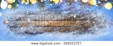 Christmas or New Year snowy seasonal wooden table with fir tree background