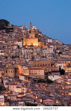 view crepuscular of dwellings and the church of Santa Margherita illuminated by street light in the city of Agira in Sicily