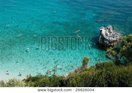 many bathers swim inside water like crystal of Mylopotamos, Greece poster