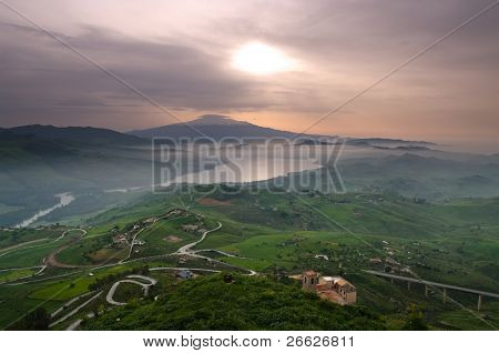 aerial view of countryside in dawn mist on the lake and on the background mount Etna. The picture was taken from Agira, Sicily