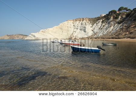 white cliffs and boats moored in the clear water of a sicilian bay