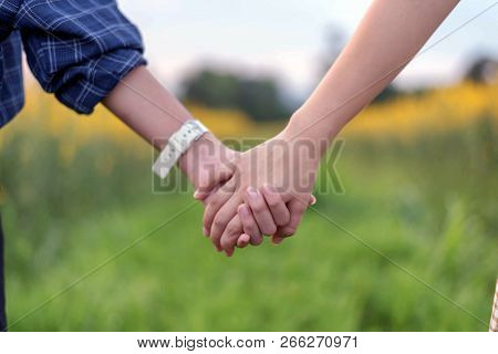 Rear View Of Two Teens Student Together Holding Hand In Hand