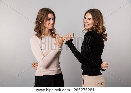 Image of two lovely women smiling and hooking each others little fingers in conciliation or friendship isolated over gray background