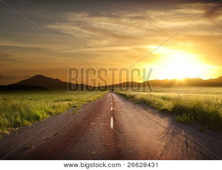 road crosses rural landscape with the silhouette of hill on background the colors of a fiery sunset