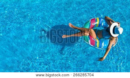 Aerial Top View Of Beautiful Girl In Swimming Pool From Above, Relax Swim On Inflatable Ring Donut A