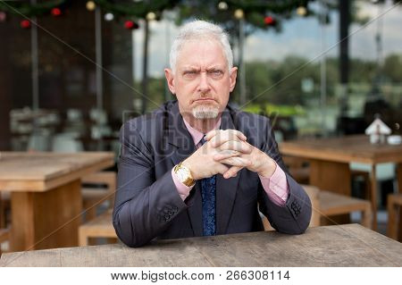Displeased frowning senior businessman sitting at table in outdoor cafe. Angry bearded man scowling and looking at camera. Sullen concept poster