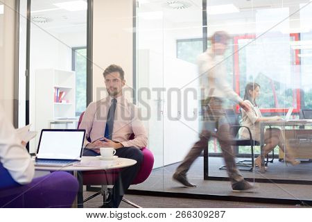 Attractive young businessman having job interview whilst people work in an active office in the background, job hunting concept
