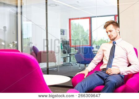 Young business man looking depressed in the office, there is no one else in the office to help or comfort him