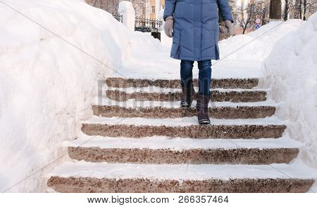 Closeup Womans Legs Goes Down On A Snowy Ladder, Staircase. Winter Park In The City During The Day I