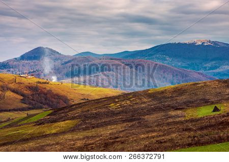 Mountainous Rural Area In Deep Autumn. Empty Fields And Leafless Trees On Hills. Cloudy November Day