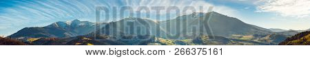 Panorama Of Mountain Ridge With Snowy Tops Above The Rural Valley. Wonderful Weather Condition Of No