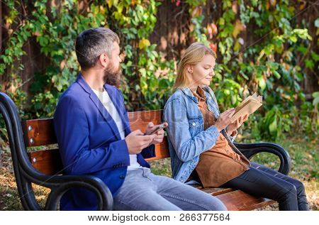 Interesting Literature. Woman Read Book While Man Read Ebook Smartphone. Man With Beard And Woman Re