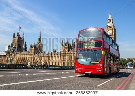 Double Decker Bus Driving On The Westminster Bridge Bridge With The Big Ben Tower Clock In The Backg