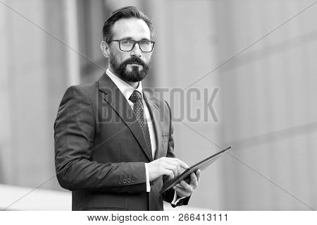 Businessman With Tablet In Hand On Background Of Office Building. Business Man Using His Tablet Out