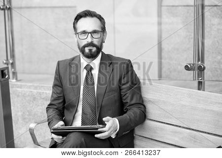 Relaxed Businessman With Tablet While Sitting On Bench. Senior Businessman Using Tablet Computer Whi
