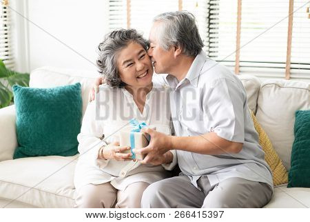 Happy Asian Senior Couple Having Anniversary Day, Bearded Husband Presenting A Packing Gift And Kiss