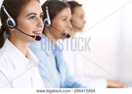 Group Of Callcenter Operators At Work. Focus At Beautiful Business Woman In Headset
