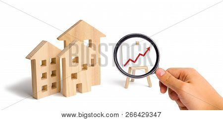 Magnifying Glass Is Looking At The Wooden Houses Stand With Red Arrow Up. Growing Demand For Housing