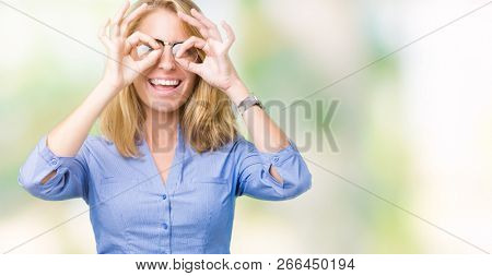 Beautiful young business woman over isolated background doing ok gesture like binoculars sticking tongue out, eyes looking through fingers. Crazy expression.