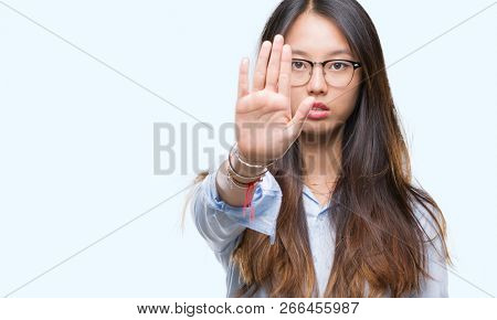 Young asian business woman wearing glasses over isolated background doing stop sing with palm of the hand. Warning expression with negative and serious gesture on the face.