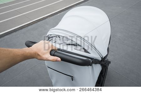 Young woman strolling a carriage outdoor. Closeup shot of male hands with grey stroller handle. Mother pushing the baby stroller around the city. Concept of active and fit parenting. poster