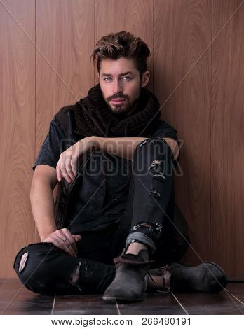 Handsome mature man sitting by the brick wall. Men's fashion.