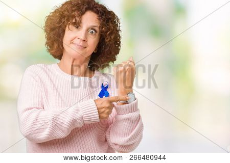 Middle ager senior woman wearing changeable blue color ribbon awareness over isolated background In hurry pointing to watch time, impatience, upset and angry for deadline delay poster