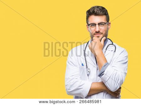 Young handsome doctor man over isolated background looking confident at the camera with smile with crossed arms and hand raised on chin. Thinking positive.