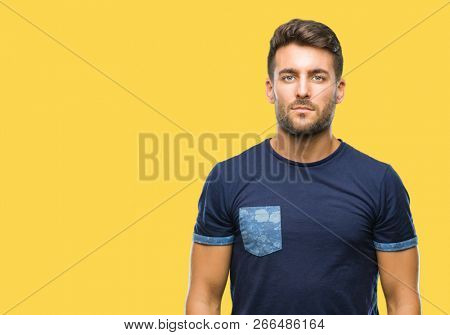 Young handsome man over isolated background with serious expression on face. Simple and natural looking at the camera.