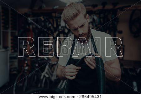 Bicycle Shop. Bicycle Repair. Salesman Holding A Tyre. Tyre Wheel On Bicycle Is Broken. Salesman Are
