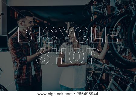 Bicycle Shop. Salesman Showing Bicycle To Customer. Woman Looking On The Customer. People Happy And