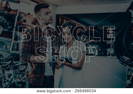 Bicycle Shop. Girl Consulting The Buyer. Woman Showing Catalog To The Customer. Customer Is Looking