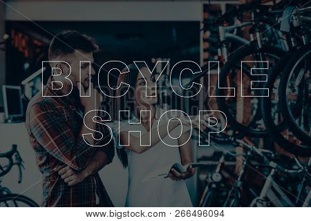 Bicycle Shop. Salesman Showing Bicycle To Customer. Woman Looking On The Bike. Woman Holding The Cat