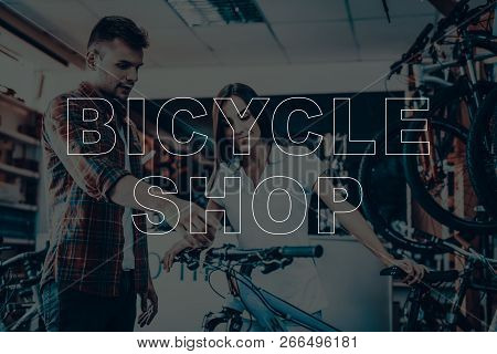 Bicycle Shop. Salesman Showing Bicycle To Customer. Man Looking On The Bike. Woman Holding The Bicyc