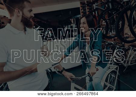Family Purchases. Customer Choosing A Bicycle. Salesman Showing Bicycle To Customer. Customer Is Wom