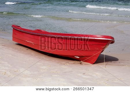 Empty Red Boat On White Sand Beach By Blue Sea Water. Seaside Activity Kayaking. Marine Guard Boat.