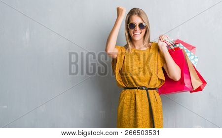 Beautiful young woman over grunge grey wall holding shopping bags on sales screaming proud and celebrating victory and success very excited, cheering emotion