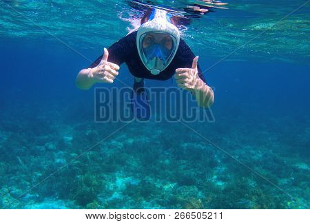 Woman Underwater Shows Thumb Up. Snorkel In Coral Reef Of Tropical Sea. Young Girl In Full-face Snor