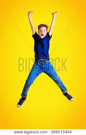 A full-length portrait of emotional funny jumping boy over the yellow background. Childhood, kids. Casual style.